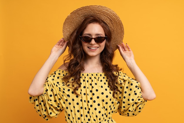 Portrait of red head woman in straw hat and stylish sunglasses posing on yellow in summer dress.