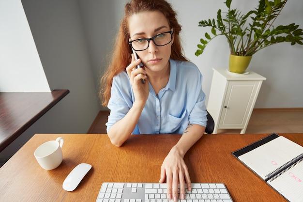 Ritratto della segretaria femminile della testarossa che ascolta attentamente alle sue istruzioni del capo sul telefono cellulare