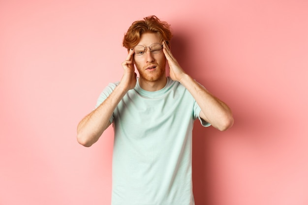 Portrait of redhead man in crooked glasses touching head and feeling dizzy or nauseous, having hangover or headache, standing over pink background.