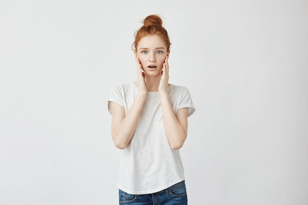 Portrait of redhead surprised woman with hands on cheeks.