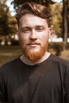 Portrait of a redhead young man with a beard and stylish haircut