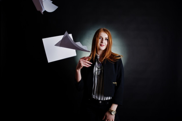 Portrait of a redheaded businesswoman in striped blouse and jacket throwing the paper away.