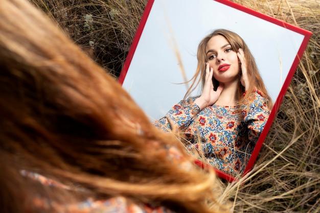 Портретное отражение в зеркале красивой девушки