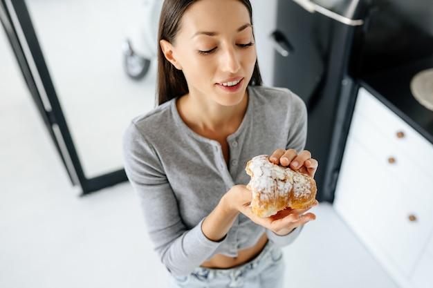 Portrait of rejoicing woman eats tasty croissant at home. unhealthy food concept.