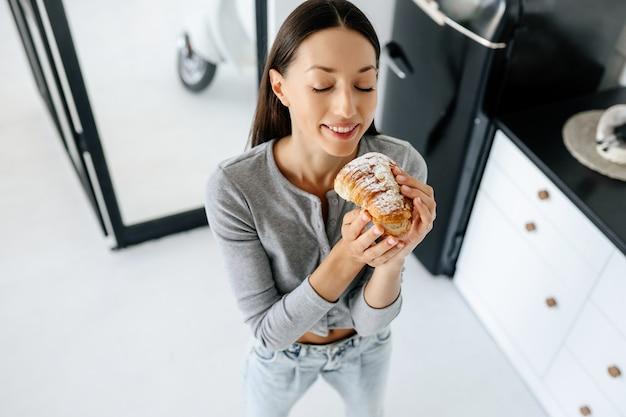 Portrait of rejoicing woman eats tasty croissant at home.
