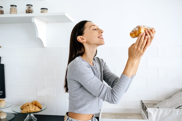 Portrait of rejoicing woman eats tasty croissant at home
