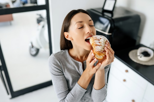 Portrait of rejoicing woman eats tasty croissant at home