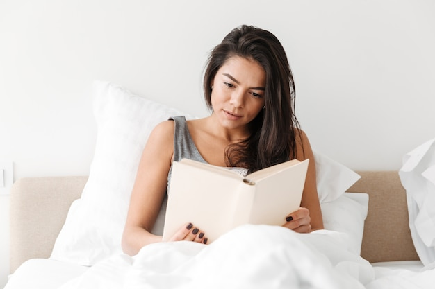 Portrait of relaxed adorable woman with long brown hair resting in comfortable bed after sleep, and reading book