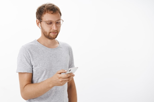 Portrait of relaxed carefree ordinary male with bristle in glasses browsing in smartphone wearing wireless earphones picking song looking in device screen