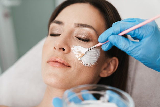 Portrait of relaxed caucasian woman getting cosmetic procedure by specialist while lying in beauty salon