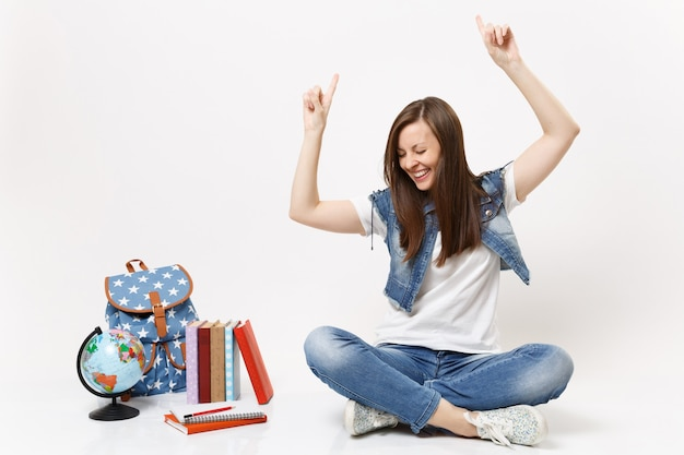 Portrait of relaxed joyful woman student with closed eyes pointing index fingers up sitting near globe, backpack school books isolated