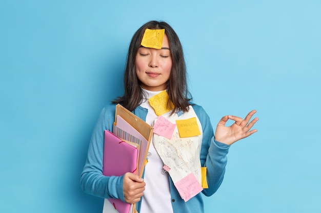 Portrait of relaxed student tries to relax meditates indoor makes okay gesture keeps eyes closed holds folders stuck with papers