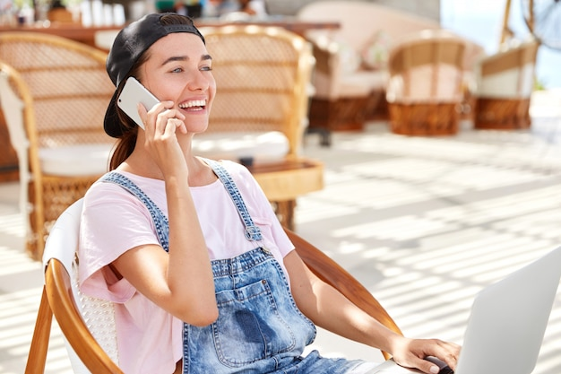 Portrait of relaxed stylish hipster woman in cap and denim overalls, enjoys communication on smart phone while recreats in coffee shop