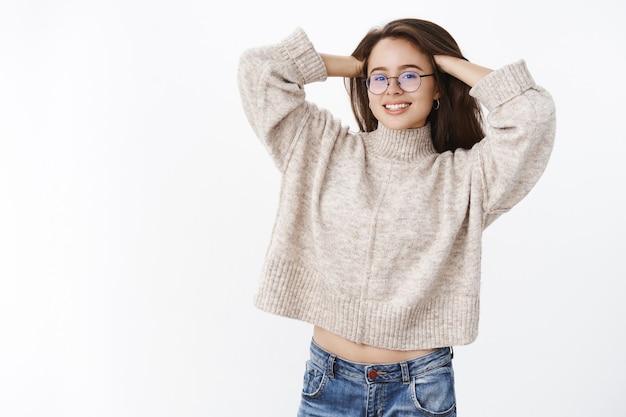 Ritratto di una donna attraente e tenera rilassata con gli occhiali e un maglione caldo ed elegante che massaggia i capelli e si allunga con gioia