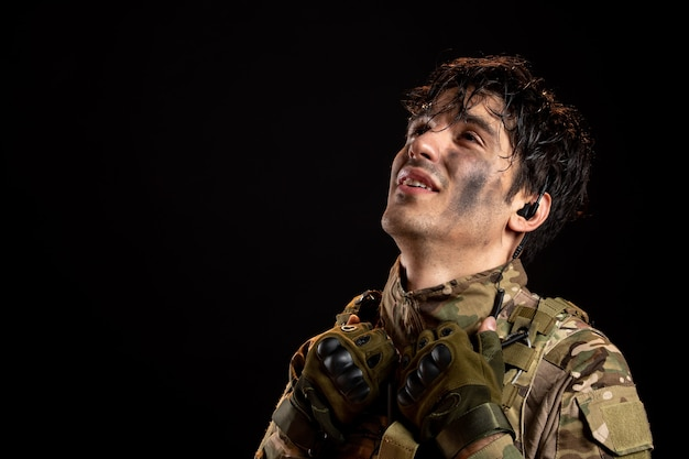Portrait of relieved young soldier in uniform on dark wall