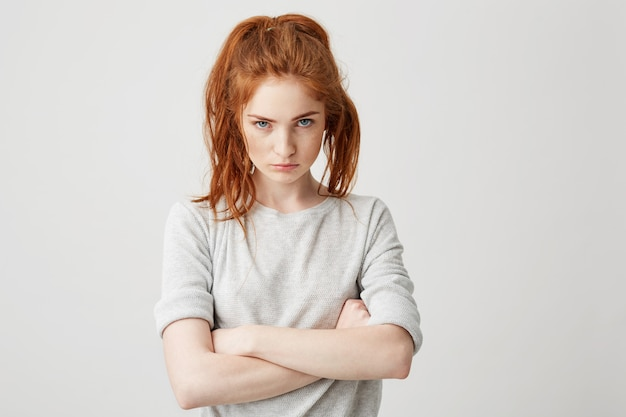 Portrait of resentful young pretty redhead girl brutally with crossed arms .