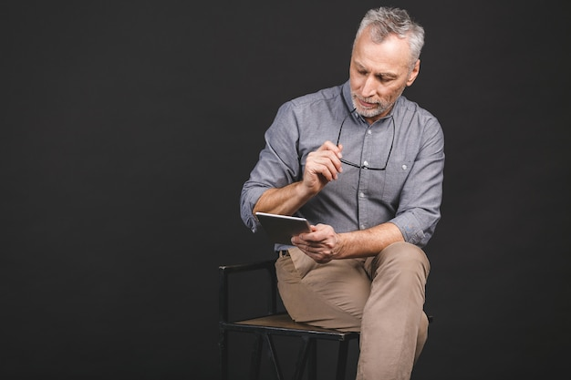 Portrait of retired senior man holding in his hand a digital tablet while sitting, holding glasses.