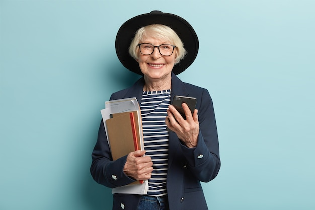 Portrait of retired teacher with grey hair, wrinkled skin, carries papers and notebook