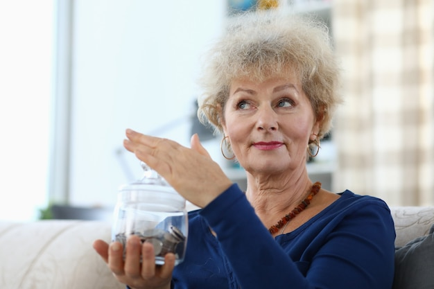 Portrait of retired woman holding glass jar piggy bank