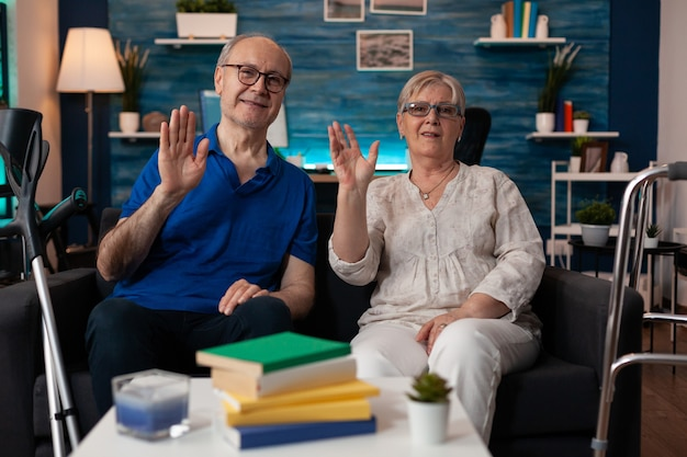 Portrait of retirement couple sitting on couch waving hands at camera in living room. old man and woman with walking disablement having crutches and walk frame for transportation support