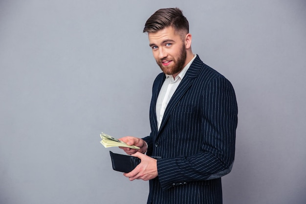 Portrait of a rich businessman holding money over gray wall and looking at camera