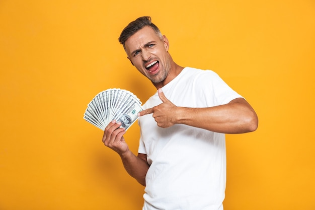 Portrait of rich guy 30s in white t-shirt smiling and holding bunch of money isolated on yellow