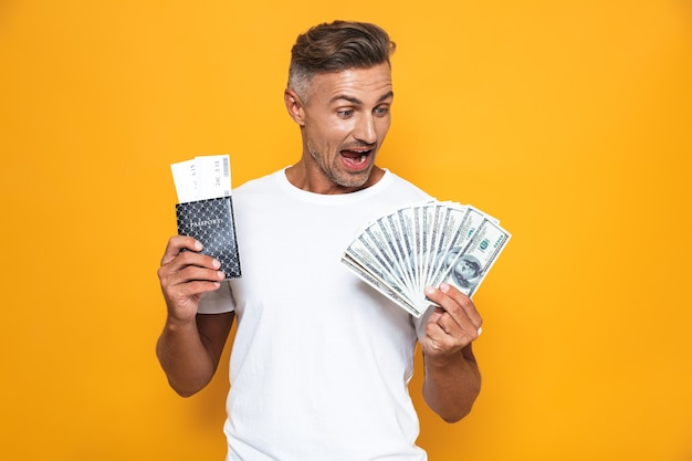 Portrait of rich man 30s in white t-shirt holding money fan and travel tickets isolated on yellow