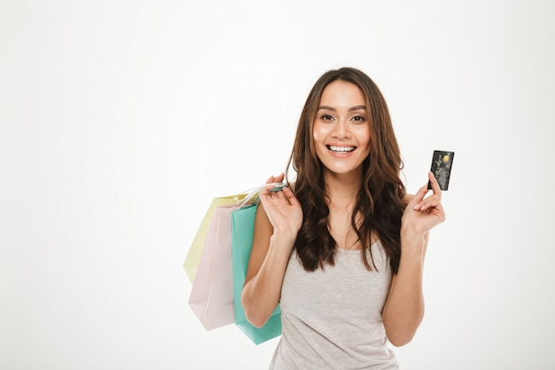 Portrait of rich and trendy woman with buying purchases and paying with credit card, isolated over white