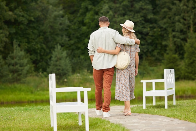Portrait of romantic adult couple embracing while walking towards river in rustic countryside scenery