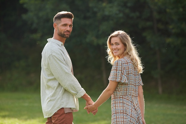 Portrait of romantic adult couple holding hands while walking on green grass in nature scenery