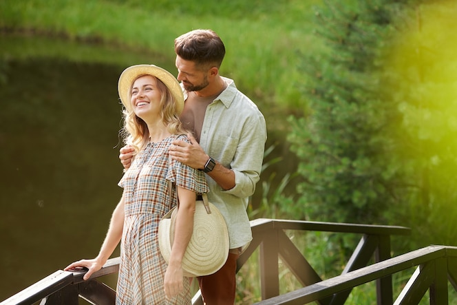 Portrait of romantic adult couple smiling happily while walking across wooden bridge by lake in rustic country scenery