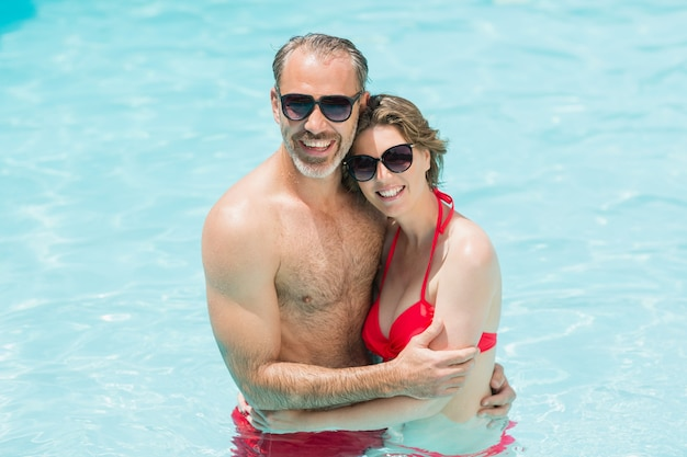 Portrait of romantic couple embracing in smiling pool