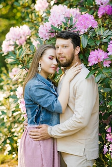 Portrait of a romantic couple in love hugging in spring in a blooming garden