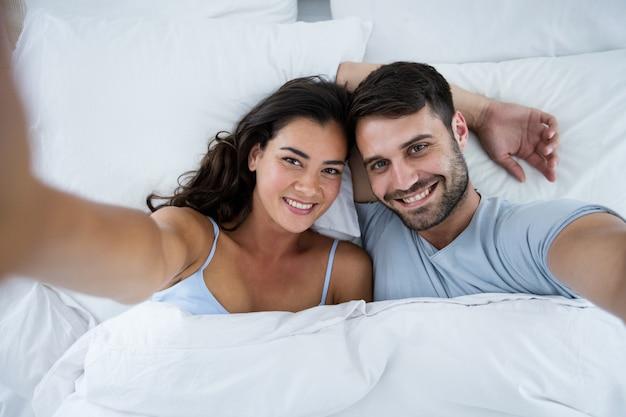 Portrait of romantic couple sleeping on bed in bedroom