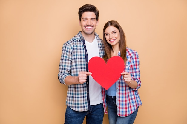 Portrait of romantic positive couple hold red paper card heart show symbol of their feelings wear checkered plaid casual style outfit isolated over pastel color background