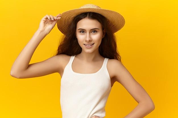 Ritratto di bella ragazza alla moda romantica che indossa canotta bianca e cappello di paglia