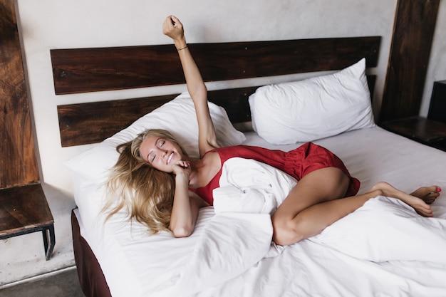 Ritratto di donna bianca romantica che si trova nella camera da letto con gli occhi chiusi. donna bionda in pigiama rosso sorridente al mattino.