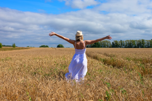 Portrait of romantic woman running across field from behind