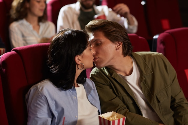 Portrait of romantic young couple kissing in cinema while enjoying romantic date , copy space