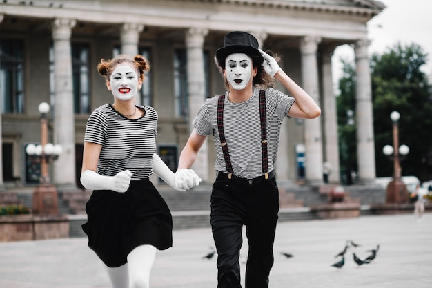 Portrait of a running mime couple