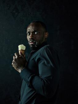 Ritratto di uomo afroamericano triste che tiene il gelato sopra il fondo nero dello studio