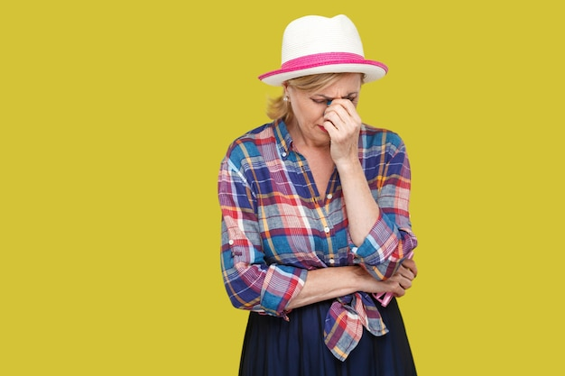 Portrait of sad alone depressed mature woman in casual style with hat standing, holding head down and crying. depression, sadness and problem of life. indoor studio shot isolated on yellow background.
