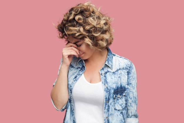 Portrait of sad alone depressed young woman with curly hairstyle in casual blue shirt standing and holding head down and crying. indoor studio shot, isolated on pink background.