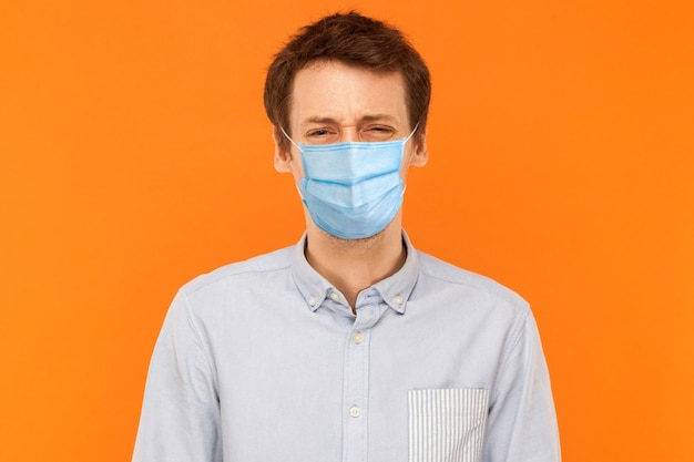 Portrait of sad alone young worker man with surgical medical mask standing and looking at camera with upset frown face. indoor studio shot isolated on orange background.