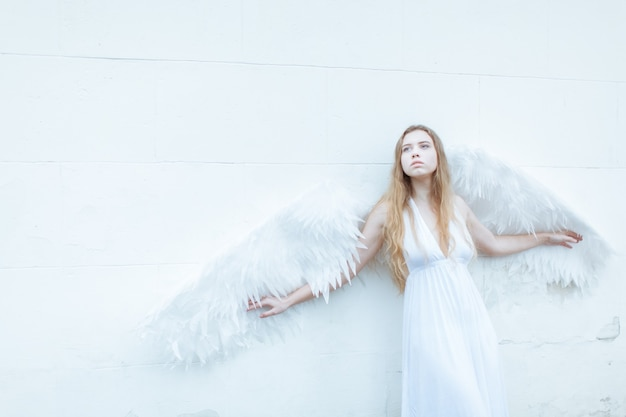 Portrait of sad angel girl with the big white wings near the white wall
