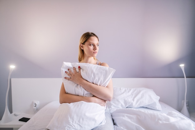 Portrait of sad attractive woman sitting on bed in bedroom and hugging pillow