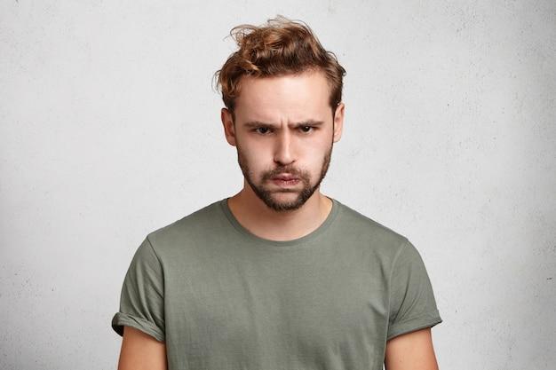 Il ritratto del giovane barbuto triste ha un'espressione scontrosa mette il broncio sulle labbra