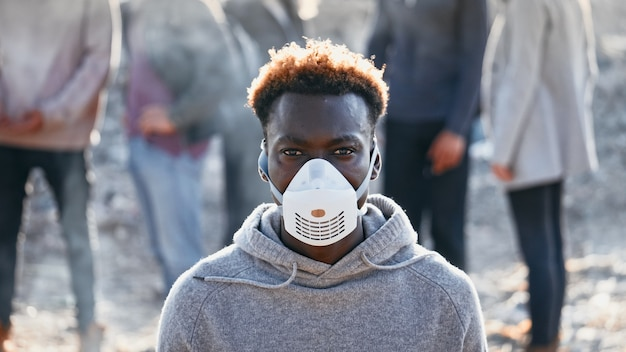 Portrait of a sad black young man in gas mask standing in toxic smoke