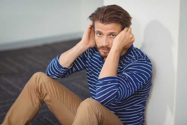 Portrait of sad business executive sitting against wall