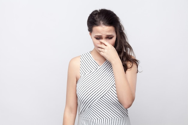 Portrait of sad depressed beautiful young brunette woman with makeup and striped dress standing, holding head down and crying. indoor studio shot, isolated on grey background.